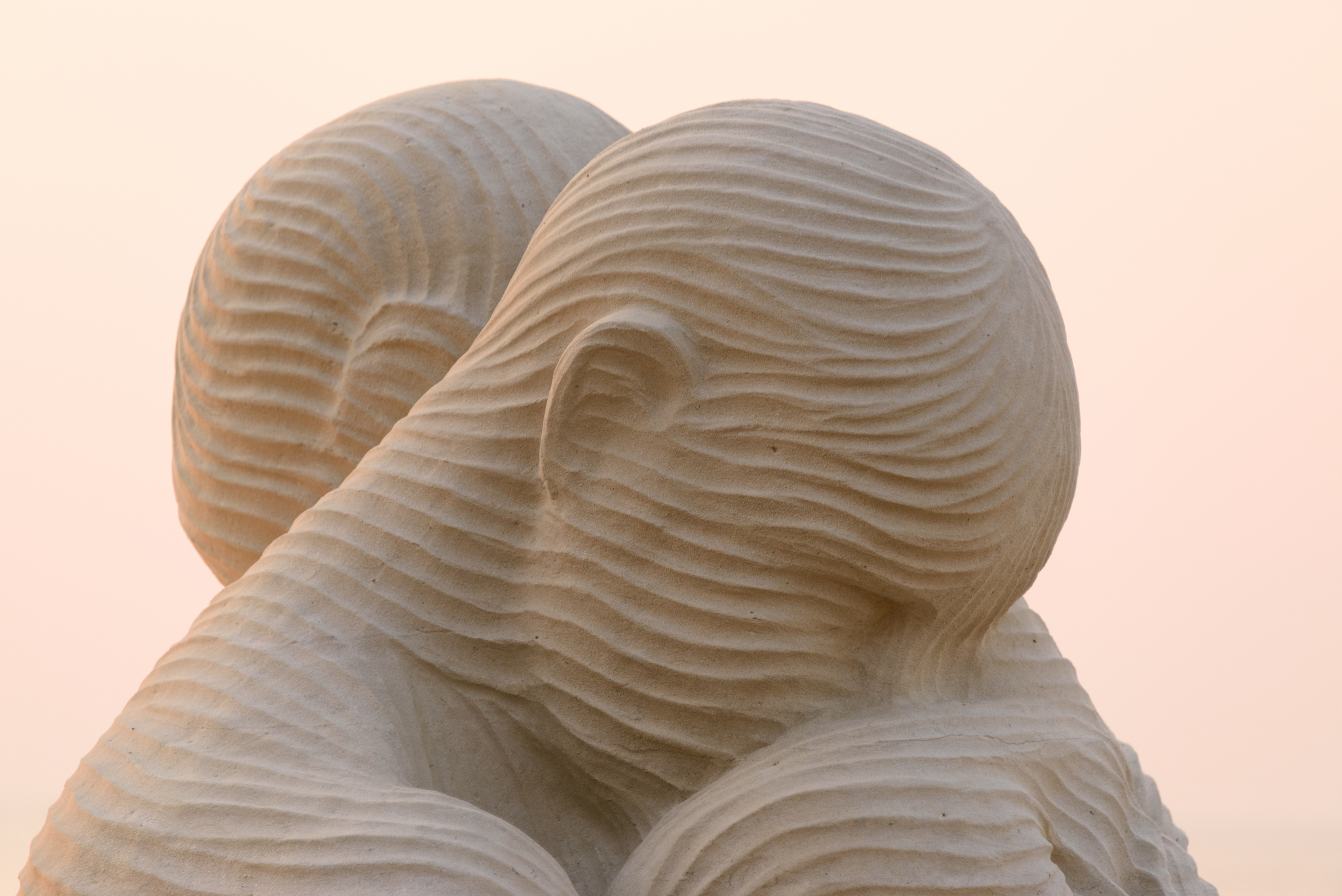 An image of a sand sculpture depicting two figures leaning against one another's shoulders.