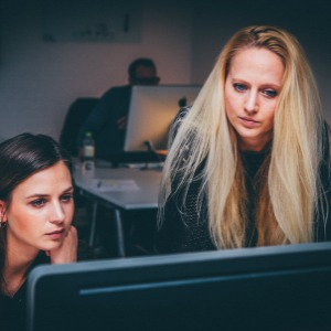Two women looking at a computer screen with concentrated expressions