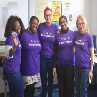 Five women with their arms around each other, smiling and wearing 'I am a #techmum'