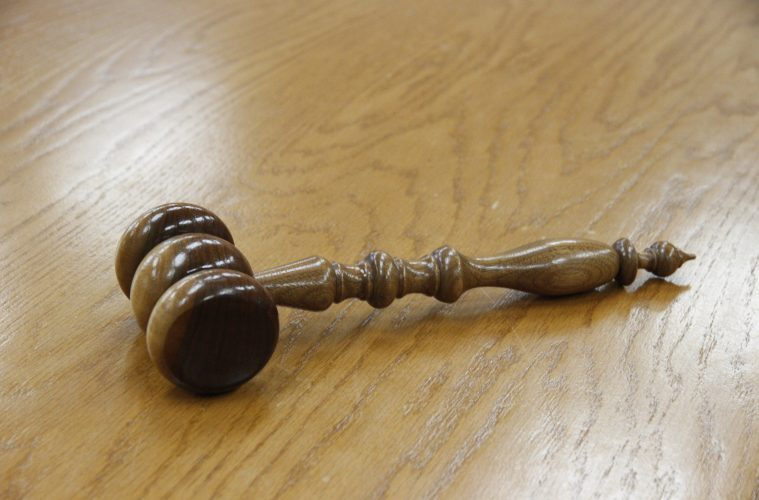 Image is of a wooden gavel placed on a wooden surface