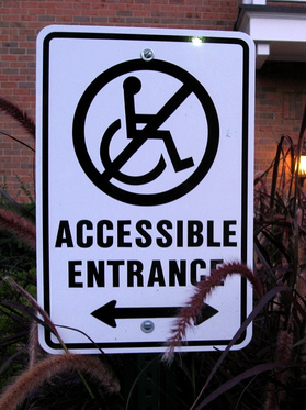 A photograph of a sign outside a building. On the sign is an illustration of the well-known 'wheelchair user' symbol with a line through it, and underneath are the words