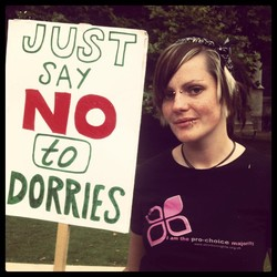 A photograph of a woman at a demonstration carrying a handmade placard which reads