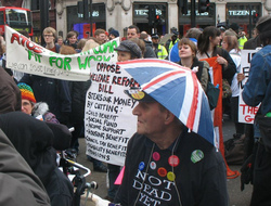 A photograph of a group of protesters. In the foreground is a man wearing a t-shirt which reads