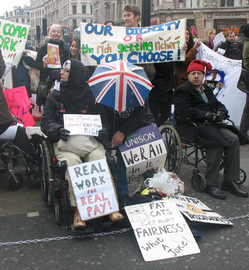 A photograph of a group of protesters. At the front are a group of wheelchair users, one holding a placard reading