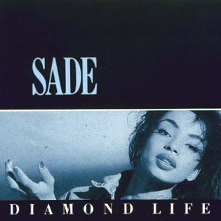 Cover of Diamond Life, the album 'When am I Going to Make a Living' is taken from. Black top half with 'SADE' in light blue. Bottom half contains light blue tinged b&w shot of Sade and thin black strip with 'DIAMOND LIFE' in white