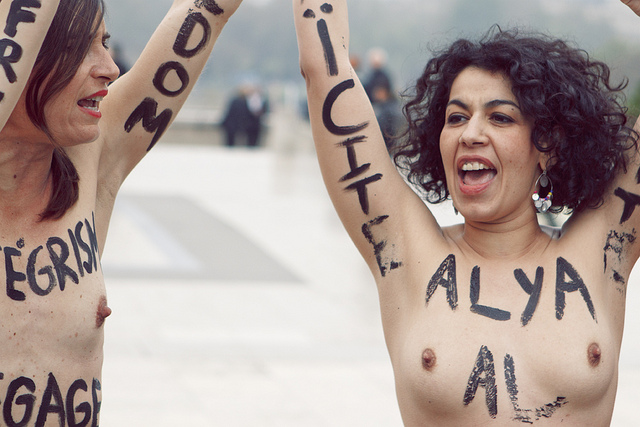 Two topless FEMEN members protest in Paris in March 2012. Both of them have their arms stretched up and they appear to be shouting. They have words written on their bodies in black. Most of these are not fully in the shot but