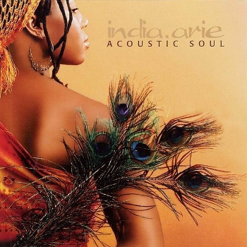 Peach coloured cover of India Arie's Acoustic Soul. Back shot of India Arie on the left, looking to her right. She wears a light orange headscarf with tassels, large hoop earrings and orange off the shoulder top or dress. A bunch of peacock feathers overlays her right shoulder and arm.