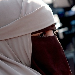 a close up photo of the veiled face of Kenza Drider, one of the women who protested against the ban in France