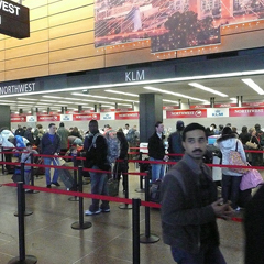 This photo is called 'The line I'm not in' and it shows a queue of people at an airport check-in. The image is from Mark Atwood's Flickr photostream and is used under the terms of The Creative Commons Attribution-NonCommercial 2.0 Generic license.