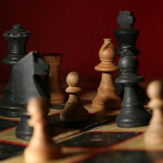 photo of black and white chess pieces on a chess board with a red background
