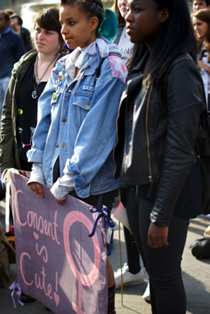 Young women hold sign, looking serious, saying