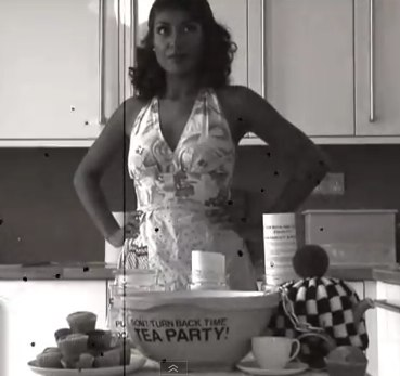 Still from Fawcett tea party video, showing a woman with arms on her hips, behind a mixing bowl labelled