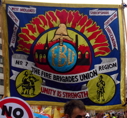 A photograph of a banner at a demonstration, of the No 7 Fire Brigade Union, with images of firefighters and the phrase