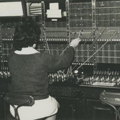 This image is called high_street_telephone_exchange_baker_bernadete_c1967. It is a monochrome photo of a woman operator working at a telephone switchboard which was found at Gawler History's Flickr photostream and is used under the terms of the Creative Commons Attribution-ShareAlike 2.0 Generic license.