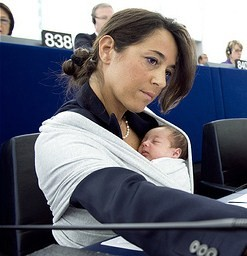 Photo of Italian MEP Licia Ronzulli voting in the European Parliament with a very small baby asleep in a sling on her chest.