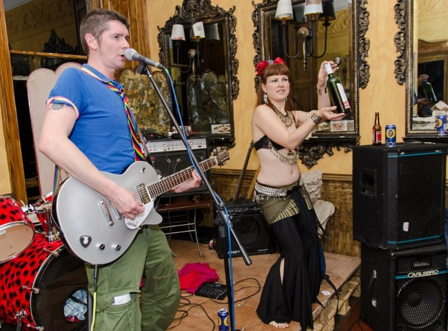 Pussy Whipped organisers Ste and Marysia onstage (daytime) in a room with retro furniture and mirrors. Marysia is on the right, holding up a bottle of wine, with speakers just in front. Ste is at the microphone with a guitar, next to a red leopard print drum kit