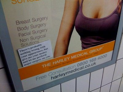 close up of a Harley Medical Group advert for cosmetic surgery, which has been stickered with a label reading