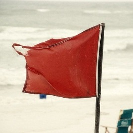 Close up photo of a red warning flag on a beach