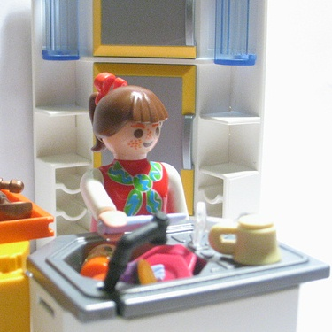 photo of a plastic, playmobil style female figurine washing up in a toy kitchen